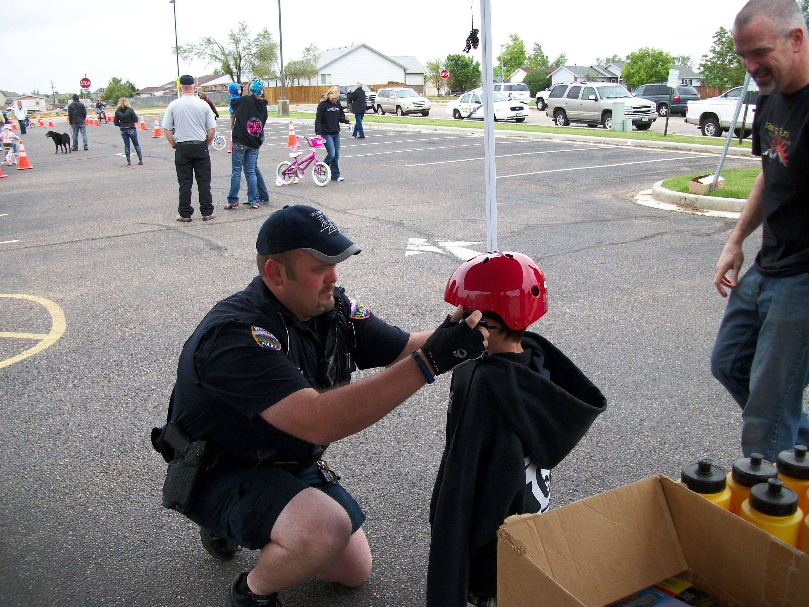 A police officer fitting a bike helmet on a young child