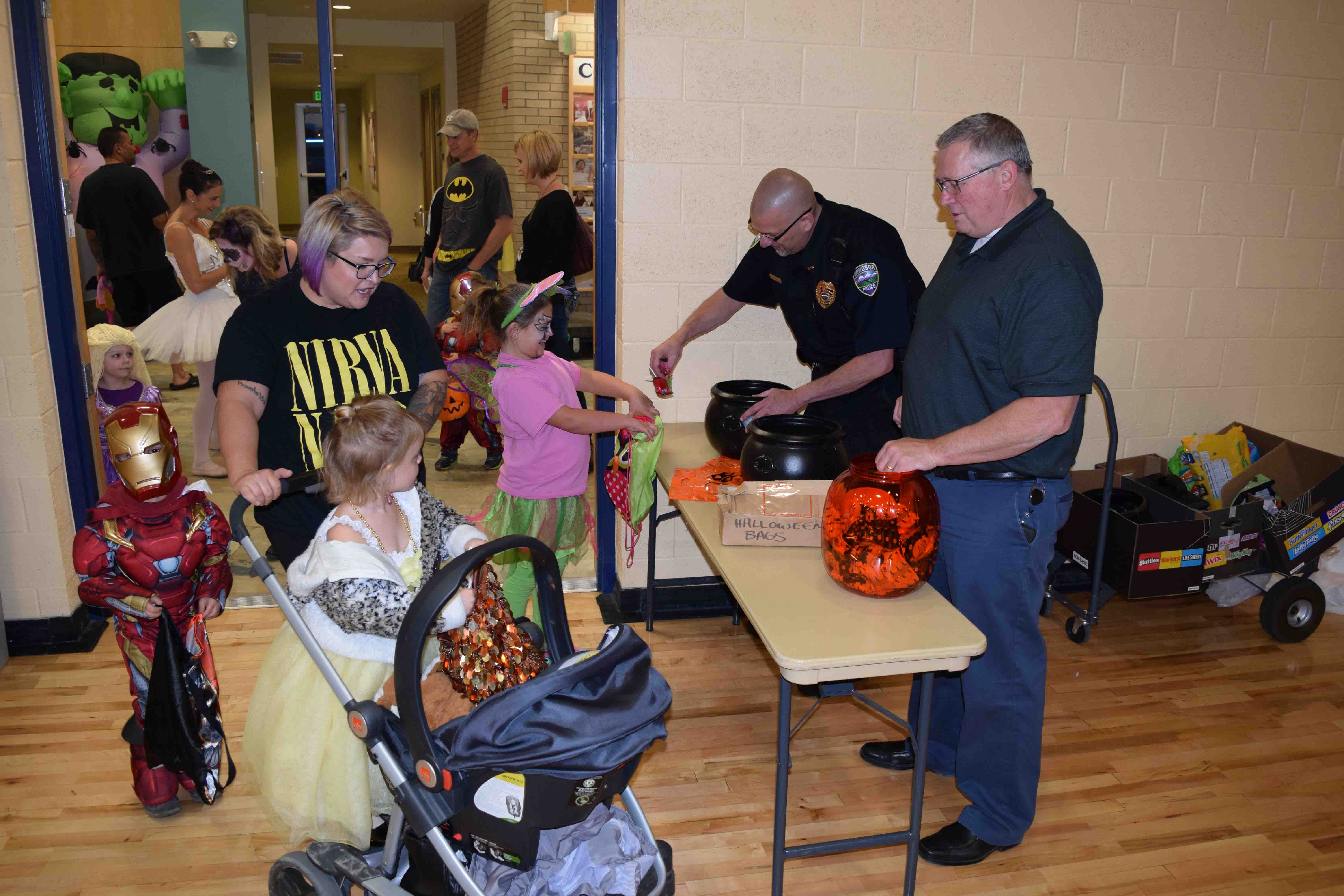 Two police officers participating in a Halloween event with young children and their parents