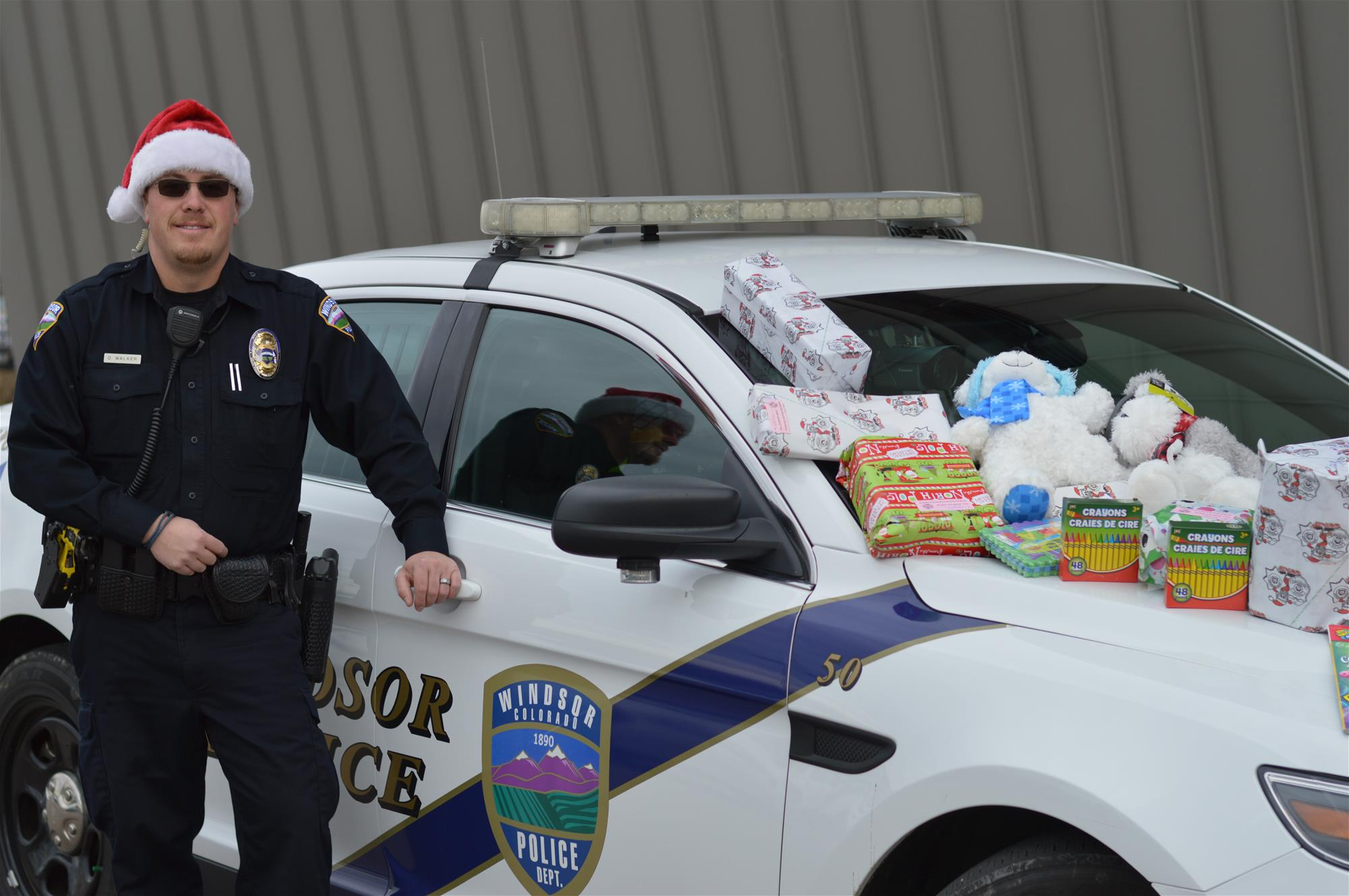 A police officer wearing a Santa hat standing next to a police cruiser with presents on the hood of